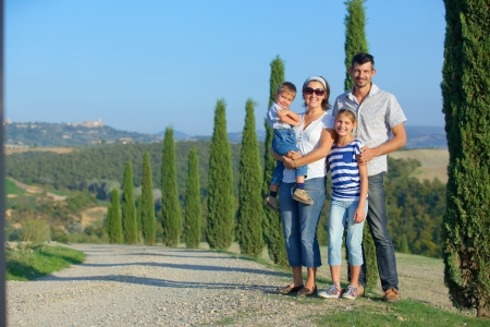 tuscan: Happy family having fun on vacations in Tuscan against cypress alley background Stock Photo