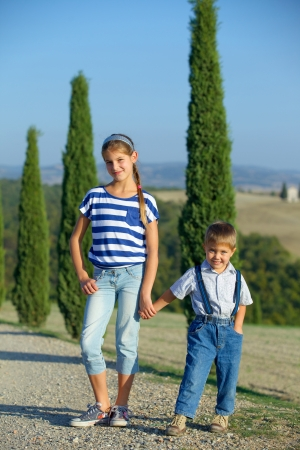 Happy sister and brother having fun on vacations in Tuscan against cypress alley background  Vertical view photo