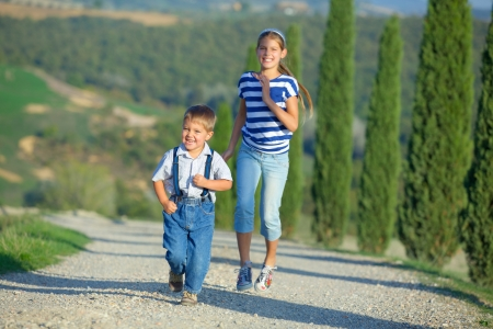 Happy sister and brother having fun on vacations in Tuscan against cypress alley background photo