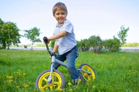 Kleiner Junge auf einem Fahrrad und seine Mutter im Sommer Park