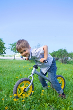 Little boy on a bicycle in the summer park photo