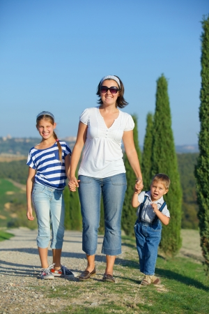Happy mother with her kids having fun on vacations in Tuscan against cypress alley background photo