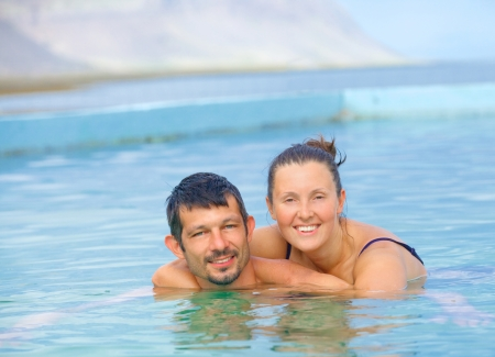 Smiling happy couple in geothermal mineral pool  Iceland photo