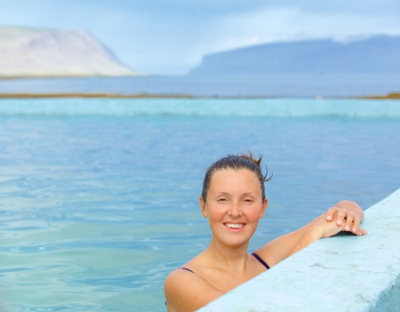 therapy geothermal: Smiling woman in bathing suit submerged in geothermal mineral pool  Iceland Stock Photo