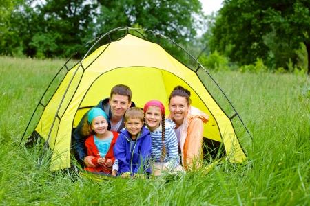 性質のキャンプでテントの中で 3 人の子供と家族