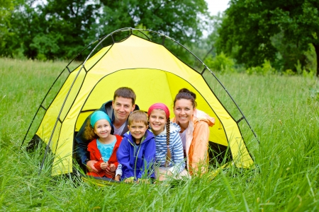 Family with three kids in tent in camping on the nature