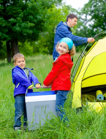 lovely sister and brother have a refrigerator with father near camp tent photo