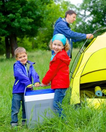 素敵な姉と弟があるキャンプ テントの近くの父と冷蔵庫
