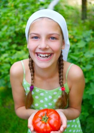 Portrait of beautiful girl holding tomato in green garden photo