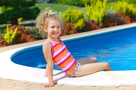 Pretty little girl sitting near swimming pool