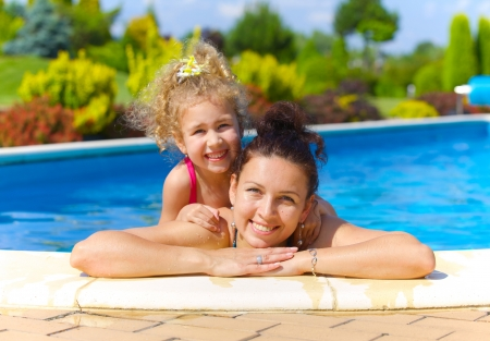 Pretty little girl with her mother in swimming pool outdoors photo