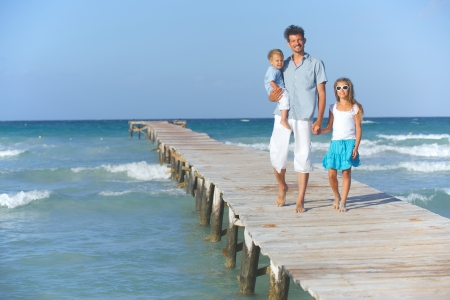 Father with his two kids walking on wooden jetty by the ocean photo