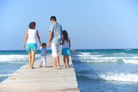 Family of four on wooden jetty by the ocean  Back view photo