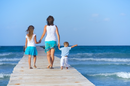 Mother with his two kids walking on wooden jetty by the ocean  Back view photo