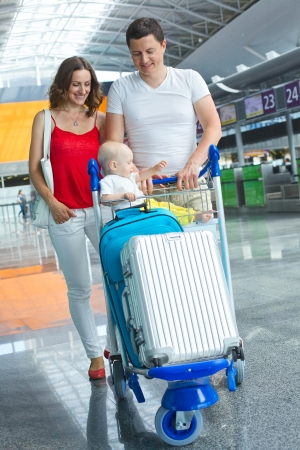 Standing traveling family with suitcases in airport photo