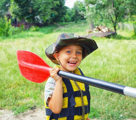 summer camp: Portrait of happy young boy holding paddle near a kayak on the river, enjoying a lovely summer day Stock Photo