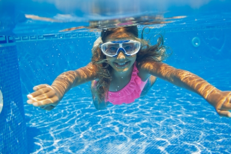Close-up portrait of the cute girl swimming underwater and smiling photo