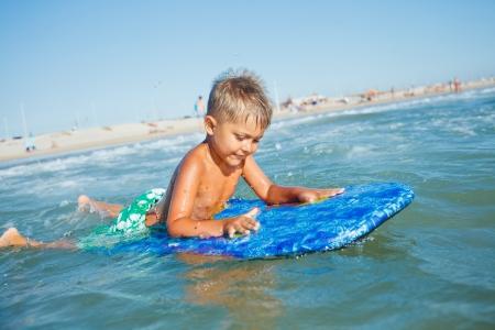Boy has fun on the surfboard in transparency sea photo