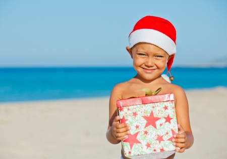 Cute little boy in Santa hat with gift on tropical vacation photo