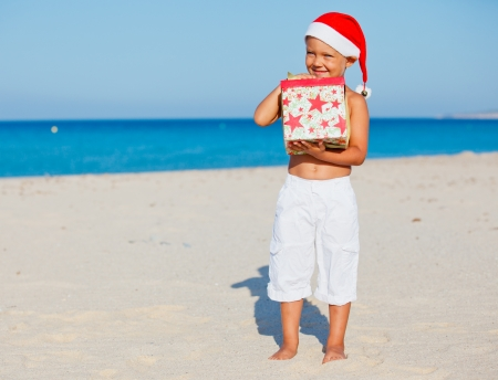 tropical christmas: Cute little boy in Santa hat with gift on tropical vacation
