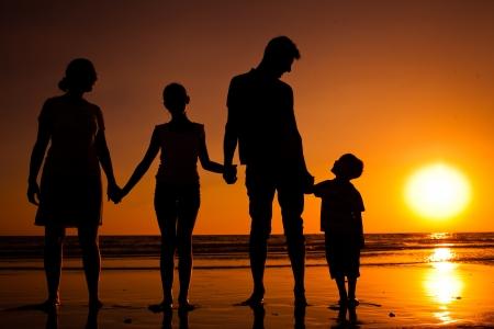 Silhouet van familie op het strand bij zonsondergang