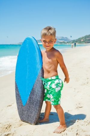 Little surfer  Boy with surfboard standing near ocean  photo