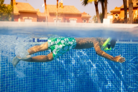 Cute little boy swimming underwater in the pool photo