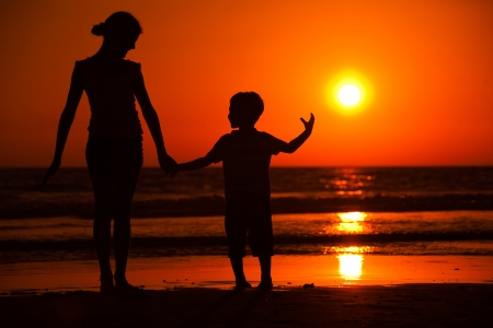 Silhouette of little brother and sister playing at the beach during sunset photo