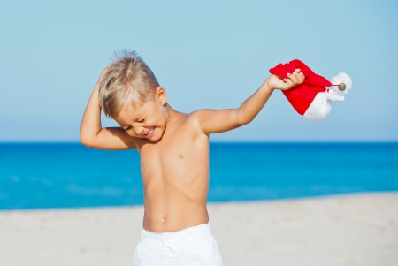 Cute little boy with Santa hat on tropical vacation photo