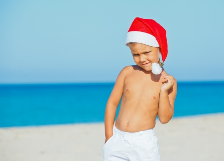 Cute little boy in Santa hat on tropical vacation photo