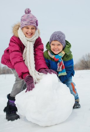 Happy beautiful children building snowman outside in winter time