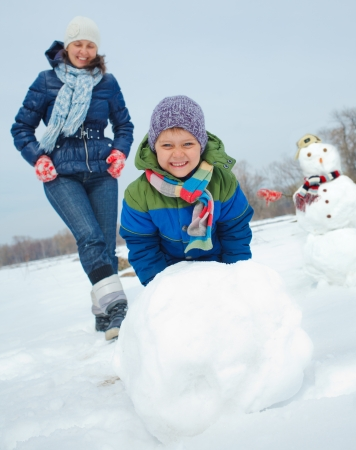 Happy beautiful boy with mother building snowman outside in winter time