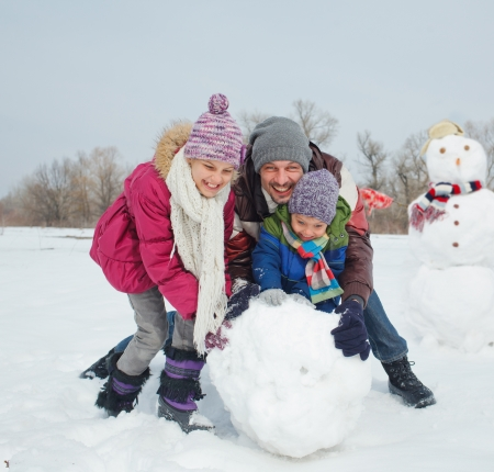 Happy beautiful children with father building snowman outside in winter time