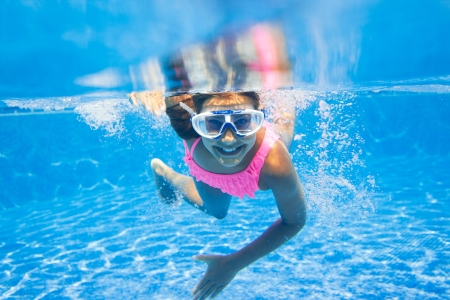 Close-up portrait of the cute girl swimming underwater