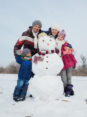 冬時間の外の雪だるまの建物 2 つの子供たちと幸せな美しい家族
