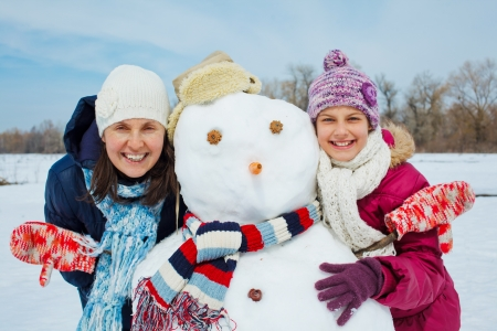 Happy beautiful girl and hers mother with snowman outside in winter time Standard-Bild