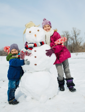 Happy beautiful children with snowman outside in winter time Stok Fotoğraf