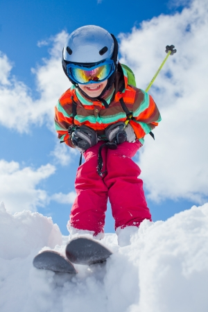 Girl on skis in soft snow on a sunny day in the mountains Standard-Bild