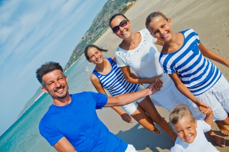 Photo of happy family with three kids running down the beach photo