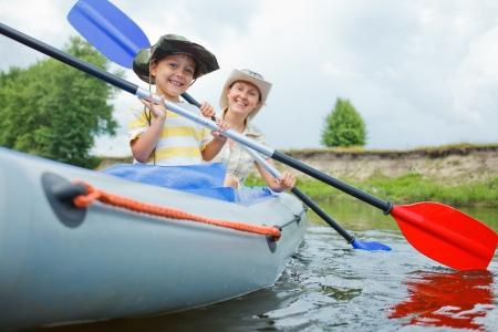 素敵な夏の日に川の母漕ぐカヤックの幸せな少年