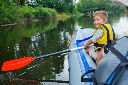 Happy young boy paddling kayak on the river and enjoying a lovely summer day photo