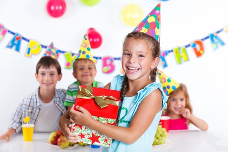 birthday party kids: Beautiful girl with giftbox looking at camera having fun at birthday party with his friends on background
