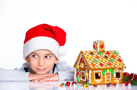 Christmas theme - Smiling boy in Santa s hat with gingerbread house, isolated on white Stok Fotoğraf