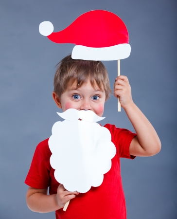 Christmas concept  Smiling funny boy in Santa red hat in studio