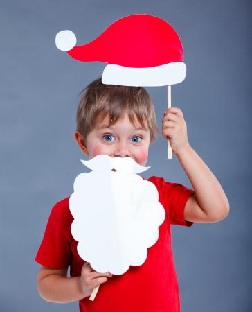 Christmas concept  Smiling funny boy in Santa red hat in studio