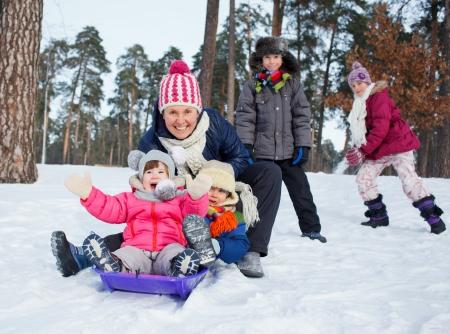 sledging: Quattro bambini con la madre � slittino in inverno-paesaggio
