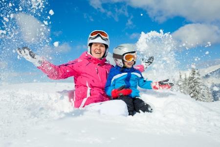 スキー、冬には、家族 - 彼の母親と冬リゾートで雪で遊ぶ少年スキー用ゴーグルとヘルメットを笑顔