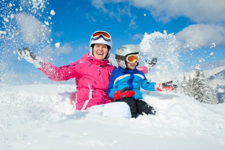 Skiing, winter, family - smiling boy in ski goggles and a helmet with his mother playing in snow in winter resort