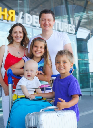 Portrait of traveling family of five with suitcases in airport photo