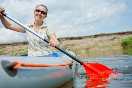 Happy woman paddling a kayak on the river, enjoying a lovely summer day photo
